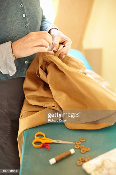 Woman sewing button on garment