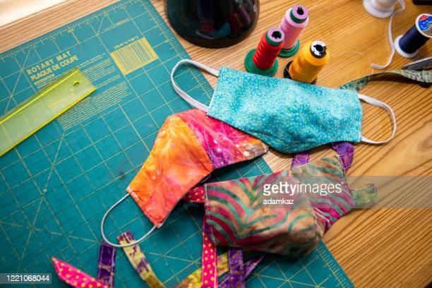 woman sewing face masks during coronavirus pandemic - adamkaz stock pictures, royalty-free photos & images
