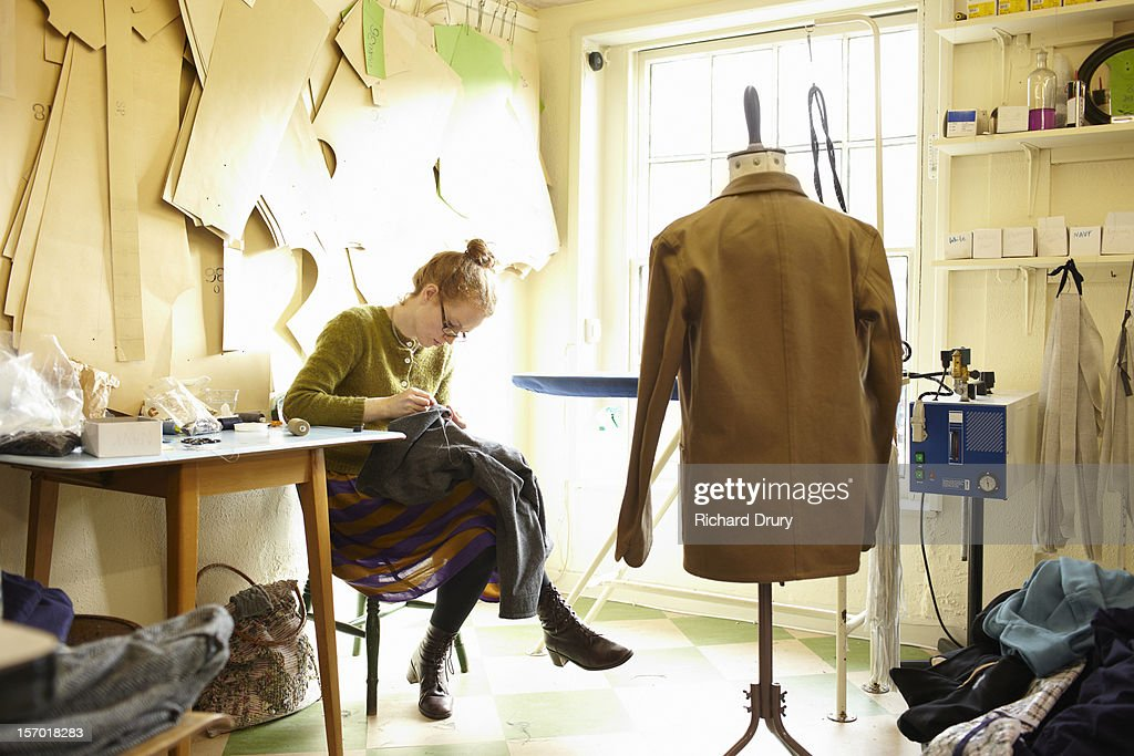 Woman sewing in clothing manufacturer's workshop : Stock Photo