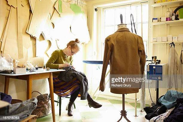woman sewing in clothing manufacturer's workshop - schneiderberuf stock-fotos und bilder