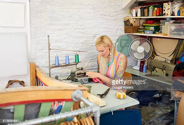 Woman sewing in vintage clothes shop.