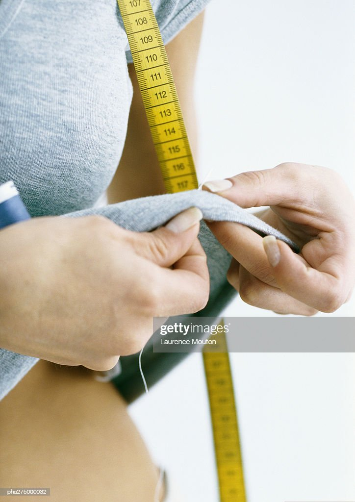 Woman sewing on tee-shirt she is wearing, close-up : Stockfoto
