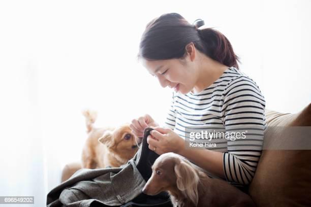 woman sewing on the sofa - 仕立て屋 ストックフォトと画像