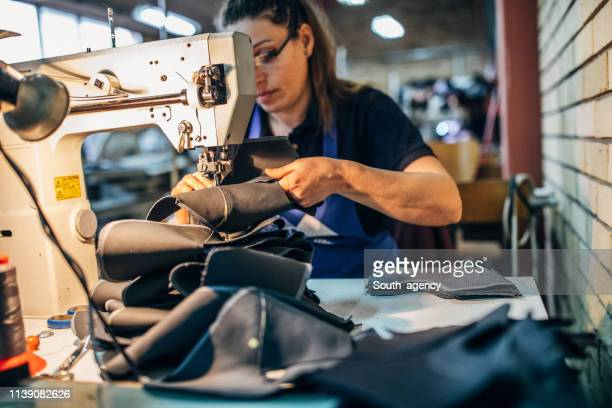 woman sewing shoes - needle plant part stock photos and pictures
