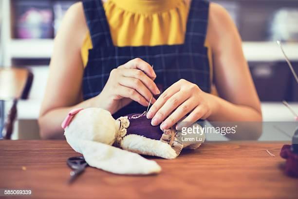 Woman sewing stuffed animal