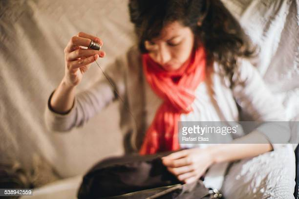 woman sewing with thimble - thimble stock photos and pictures