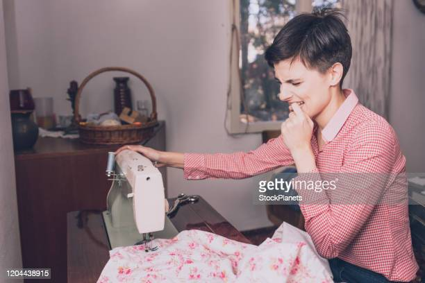 woman sews and stabs her finger on sewing machine. - finger injury stock pictures, royalty-free photos & images