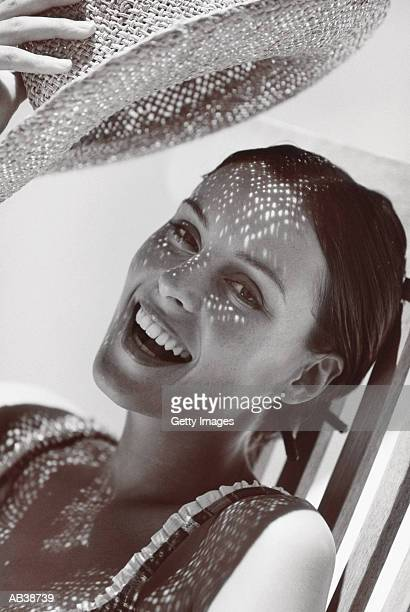 Woman shading her face from sun with hat, close-up, (B&W)