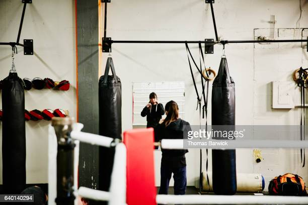 Woman shadow boxing in mirror while working out in fighting gym