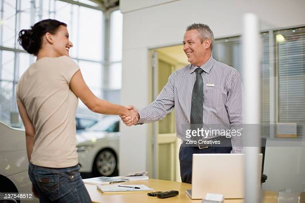 woman shaking hands with car salesman - salesman stock photos and pictures