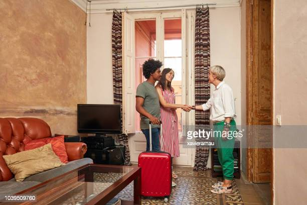 woman shaking hands with female realtor at home - house rental stock pictures, royalty-free photos & images