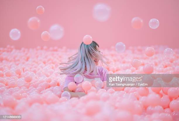 woman shaking head while sitting in ball pool against pink background - abundance stock pictures, royalty-free photos & images