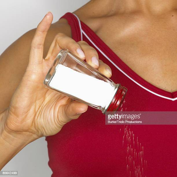 Woman shaking saltshaker