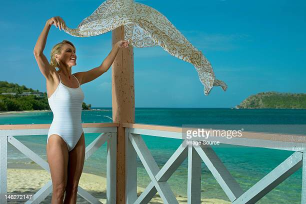Woman shaking sarong in breeze by the ocean