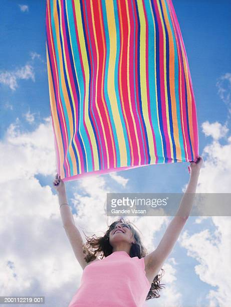 Woman shaking stripey towel, outdoors, low angle view
