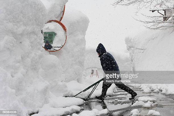 Woman shaovels snow accumulated on street on January 11 2005 in Tsunanmachi Niigata Prefecture Japan The record snowfall has killed about 70 people...