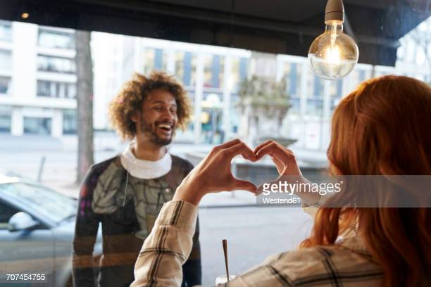 Woman shaping heart with her hands for man behind windowpane