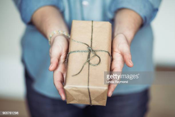 woman sharing a christmas gift - geben stock-fotos und bilder