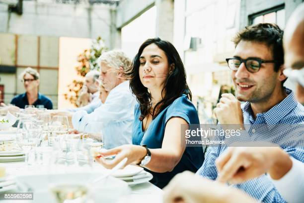 Woman sharing a meal with friends on restaurant patio