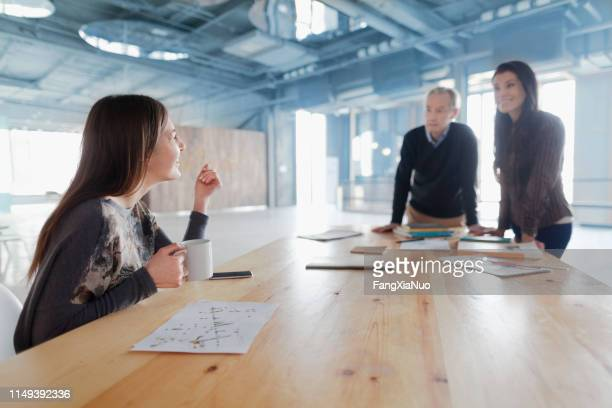woman sharing design idea at table with colleagues - initiative stock pictures, royalty-free photos & images
