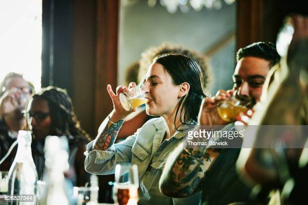 woman sharing drinks with friends in bar - beer alcohol stock pictures, royalty-free photos & images