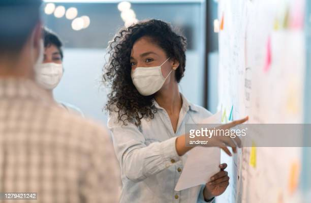 woman sharing ideas with her team at a creative office while wearing facemasks - business plan stock pictures, royalty-free photos & images