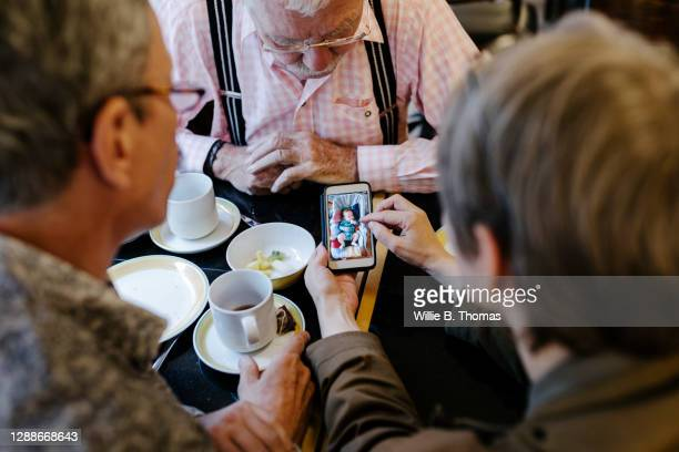 woman sharing pictures on smartphone with family during breakfast - women in suspenders stock pictures, royalty-free photos & images