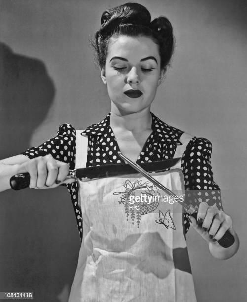 A woman sharpening a kitchen knife circa 1940