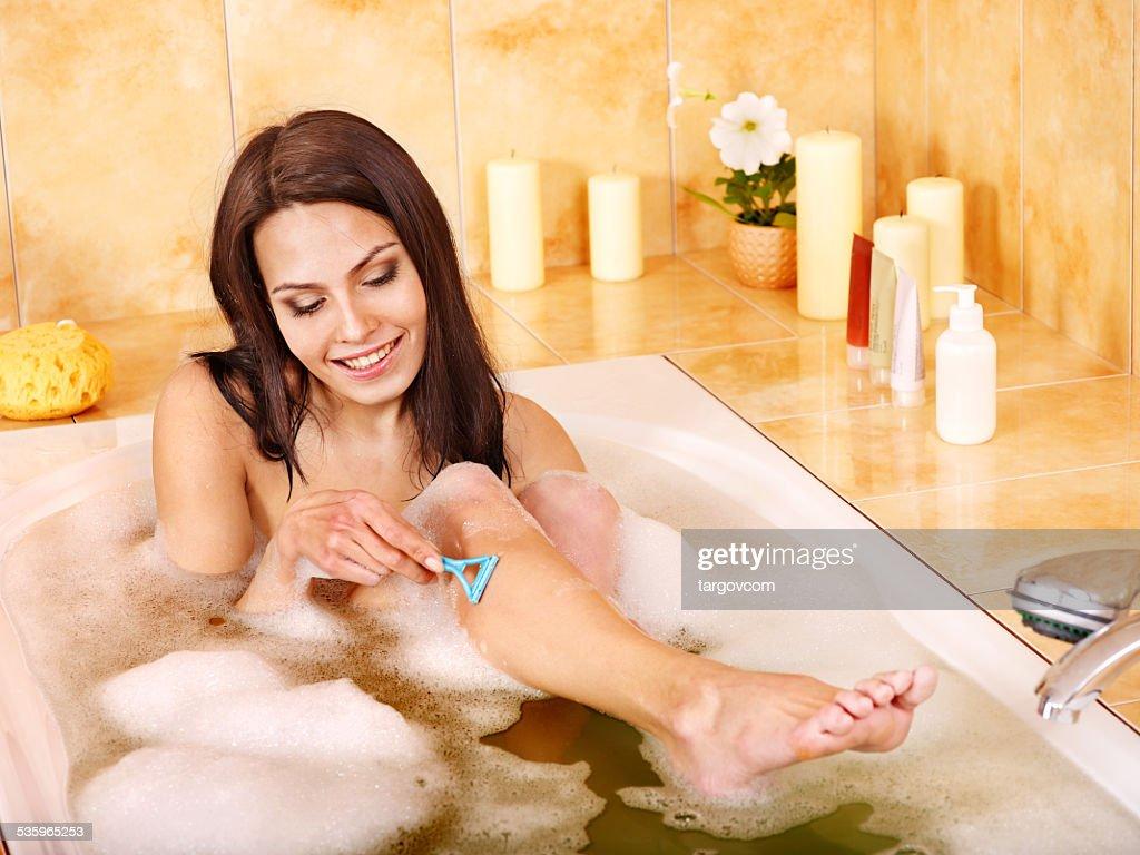 Woman shaving her legs in  bath : Stock Photo