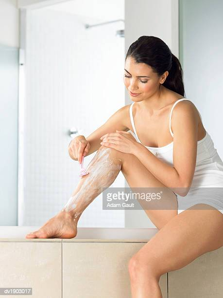 woman shaving her legs in her bathroom - frau in slip stock-fotos und bilder