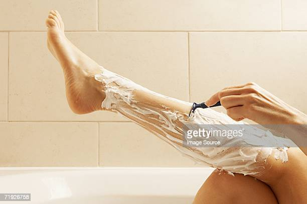 woman shaving her legs - leg stock pictures, royalty-free photos & images