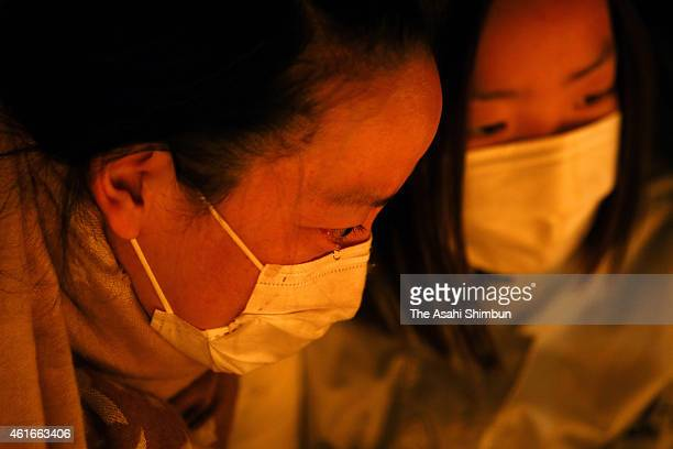 A woman sheds tear while praying for the victims in front of the candlelit bamboo lanterns to mark the 20th anniversary at Higashi Yuenchi Park on...