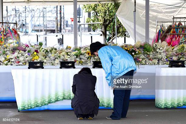 A woman sheds tears after offering flowers at an altar on the eleventh anniversary of the train derailment accident on April 25 2016 in Amagasaki...