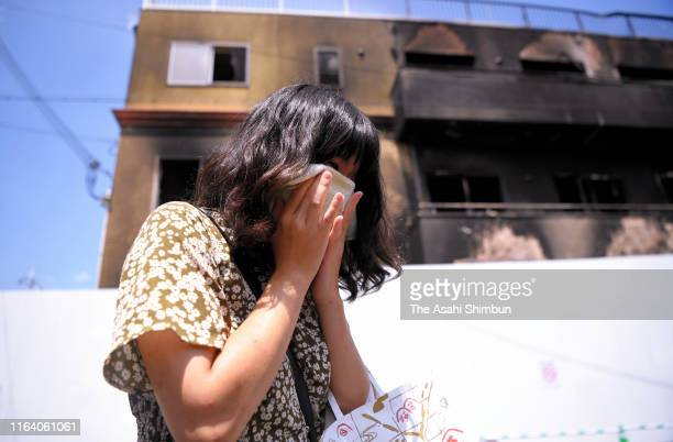 A woman sheds tears at the burnt Kyoto Animation studio a week after the arson on July 25 2019 in Kyoto Japan Thirtyfour people were killed after...