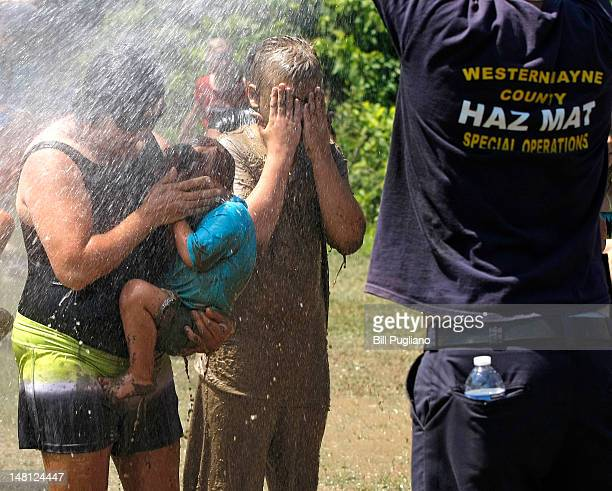 A woman sheilds her child's face from the spray of a fire hose while having mud washed off of them after playing in a giant lake of mud at the 25th...