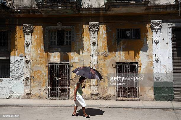 A woman shelters from the heat under an umbrella as she walks along a street on September 18 2015 in Havana Cuba Pope Francis is due to make a three...