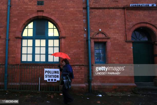 A woman shelters from the rain beneath an umbrella as she passes a sign for a polling station on Coronation Street in Salford northern England as...