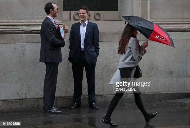 A woman shelters from the rain beneath an umbrella as she walks past talking men in the City of London on April 4 2018 Employers with more than 250...