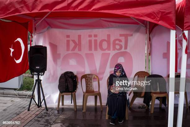 A woman shelters from the rain in an 'EVET' campaign tent on March 31 2017 in Konya Turkey Konya with a population of more than 17million is an AKP...