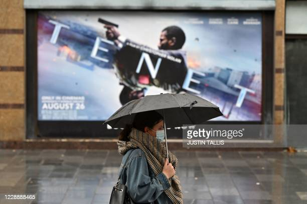 A woman shelters from the rain under an umbrella as she passes an advert for a screening of 'Tenet' outside a cineworld cinema in Leicester Square in...