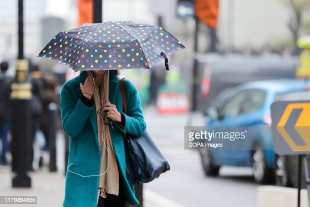 A woman shelters from the rain underneath an umbrella on a wet day 70mm rain expected as UK braces for heavy showers and gale force winds this weekend
