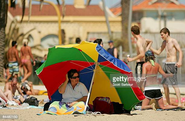 A woman shelters from the sun under an umbrella at St Kilda beach as a heatwave hits Melbourne on January 27 2009 in Melbourne Australia The...