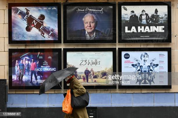 A woman shelters under an umbrella as she passes advertisements for screenings outside a Picturehouse cinema in west London on October 4 2020...
