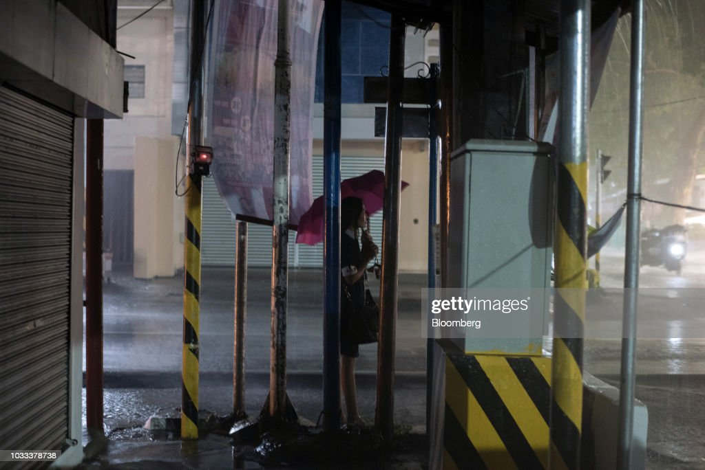 A woman shelters under an umbrella during heavy rainfall ahead of Typhoon Mangkhut's arrival in Tuguegarao, Cagayan province, the Philippines, on Friday, Sept. 14, 2018. Super Typhoon Mangkhut is expected to threaten Chinas Guangdong coastline, and Hong Kong, with a possible direct strike that may cause as much as $120 billion in damage and economic losses. Photographer: Carlo Gabuco/Bloomberg via Getty Images
