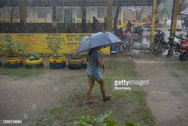 A woman shelters under an umbrella during heavy rainfall outside the temporary evacuation center at Balzain East Elementary School ahead of Typhoon...