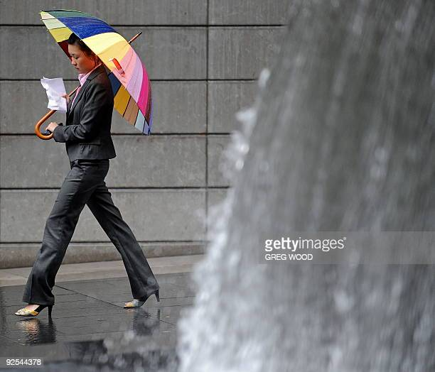 A woman shelters under an umbrella during wet and windy conditions as she walks past a water fountain feature at the start of the working week in...