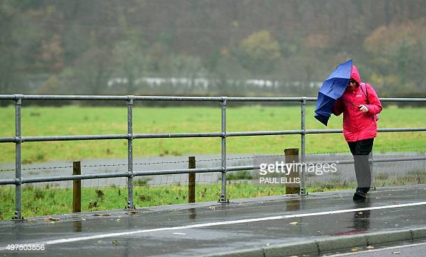 A woman shelters under an umbrella in Machynlleth in mid Wales on November 17 2015 The river levels are high following prolonged rain and the...