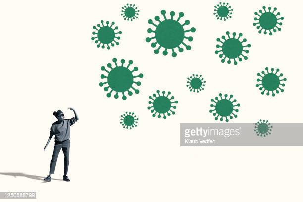 woman shielding eyes by large green coronavirus - spread stock pictures, royalty-free photos & images