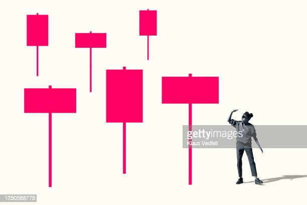 woman shielding eyes by large pink placards - democracy stock pictures, royalty-free photos & images