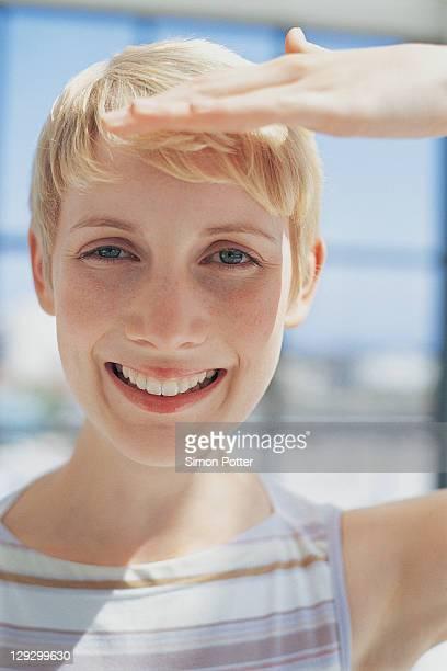 Woman shielding eyes from sun
